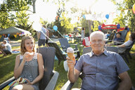 Portrait carefree senior man eating ice cream cone with daughter at summer neighborhood block party in park - HEROF08724
