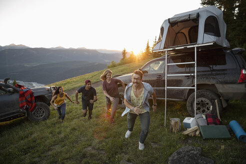 Playful friends outside SUV with rooftop tent on mountain hillside, Alberta, Canada - HEROF08751
