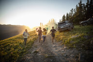 Playful friends running with smoke bombs on remote road, Alberta, Canada - HEROF08754