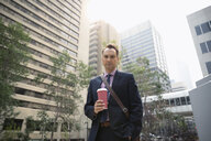Portrait confident businessman with coffee in city - HEROF08763