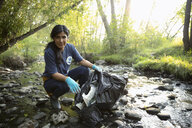 Portrait confident woman volunteering, cleaning up garbage in stream - HEROF08787