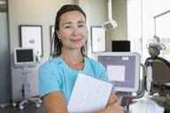 Portrait confident female dental hygienist in dentist office - HEROF08907