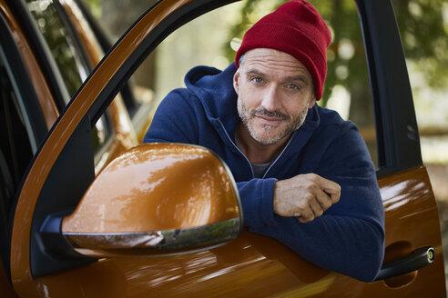 portrait mann mit roter mütze, lehnt an autotür, outdoor - PNEF01188