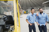 Portrait of workers near forklift in manufacturing plant - HEROF09002