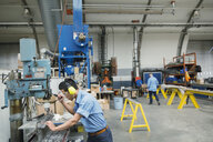 Worker operating drill machinery in manufacturing plant - HEROF09008