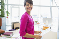 Portrait of smiling businesswoman with paperwork in office - HEROF09029