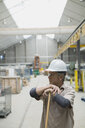 Worker with broom in manufacturing plant - HEROF09077