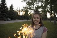 Portrait smiling young woman with sparklers in park - HEROF09125