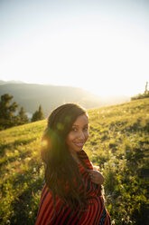 Portrait smiling young woman wrapped in blanket on sunny, idyllic hillside - HEROF09152