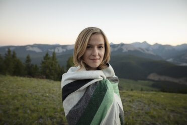 Portrait smiling, carefree woman wrapped in blanket in mountain field, Alberta, Canada - HEROF09155
