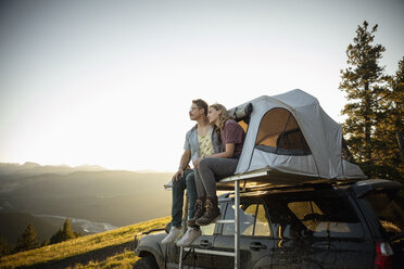 Serene couple relaxing at SUV rooftop tent in idyllic mountain field, Alberta, Canada - HEROF09158