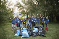 Portrait enthusiastic volunteers cheering, cleaning up garbage in park - HEROF09185