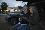 Senior couple with digital tablet at back of SUV at night - HEROF09206