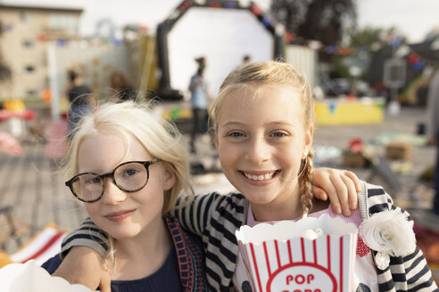 Portrait smiling, confident sisters with popcorn at movie in the park - HEROF09227