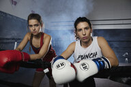 Portrait tough female boxers in boxing ring - HEROF09293
