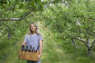 Portrait smiling, confident female farmer holding bottles of apple cider in vineyard - HEROF09299