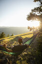 Serene man drinking coffee in sunny hammock with idyllic mountain view, Alberta, Canada - HEROF09332
