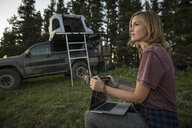Thoughtful woman camping, using laptop near SUV with rooftop tent - HEROF09335