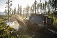 SUV splashing through mud on sunny remote road, overland adventure, Alberta, Canada - HEROF09338