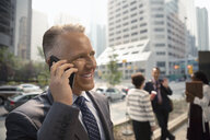 Smiling businessman talking on smart phone on city sidewalk - HEROF09356