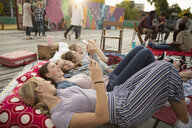 Teenage girls hanging out, relaxing and using smart phones in urban park - HEROF09392