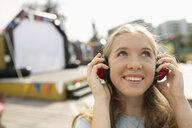 Smiling teenage girl with headphones in sunny park - HEROF09404