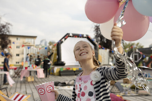 Smiling, enthusiastic girl with balloons and popcorn at movie in the park - HEROF09416