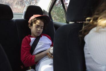 Tired Latinx boy in baseball uniform sleeping in back seat of car - HEROF09458