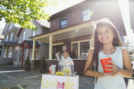 Smiling girl with cup at lemonade stand - HEROF09572