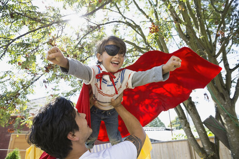 Father flying son in superhero cape overhead - HEROF09575
