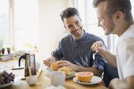 Homosexual couple enjoying breakfast at table - HEROF09587