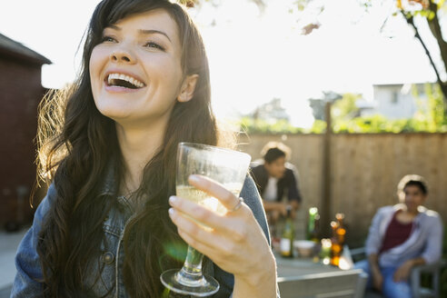 Laughing woman drinking wine at backyard barbecue - HEROF09596