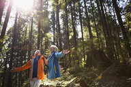 Senior couple with arms outstretched in sunny woods - HEROF09632
