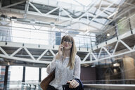 Businesswoman talking on cell phone in airport atrium - HEROF09689