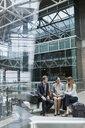 Business people using digital tablet in airport atrium - HEROF09692