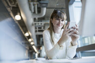 Businesswoman texting on cell phone at office desk - HEROF09704