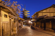 Traditional houses lining a narrow street with a pagoda in the distance, Higashiyama at night, Kyoto, Japan. - MINF10089