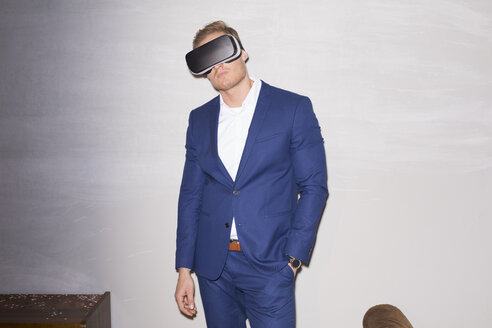 Young man wearing blue suit using Virtual Reality Glasses - PNEF01207