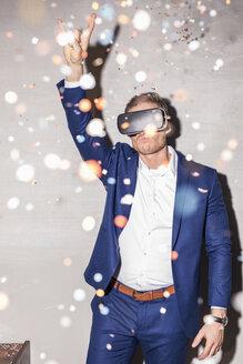 junger mann in anzug und virtual reality brille auf party in konfetti regen studio, münchen, deutschland - PNEF01210