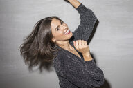 Portrait of laughing young woman dancing at party - PNEF01216