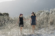 South Africa, Western Cape, Hout Bay, two young women walking in the dunes while talking - LHPF00400