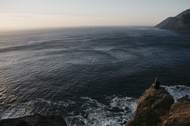 South Africa, Western Cape, woman sitting on a rock looking at view, seen from Chapman's Peak Drive - LHPF00409