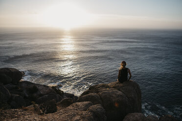 South Africa, Western Cape, woman sitting on a rock watching sunset, seen from Chapman's Peak Drive - LHPF00412
