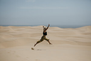 Namibia, Walvis Bay, Namib-Naukluft National Park, Sandwich Harbour, woman jumping in dune landscape - LHPF00430