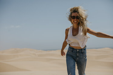 Namibia, Walvis Bay, Namib-Naukluft National Park, Sandwich Harbour, happy woman in dune landscape - LHPF00433