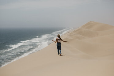 Namibia, Walvis Bay, Namib-Naukluft National Park, Sandwich Harbour, woman walking in dune landscape at the sea - LHPF00436