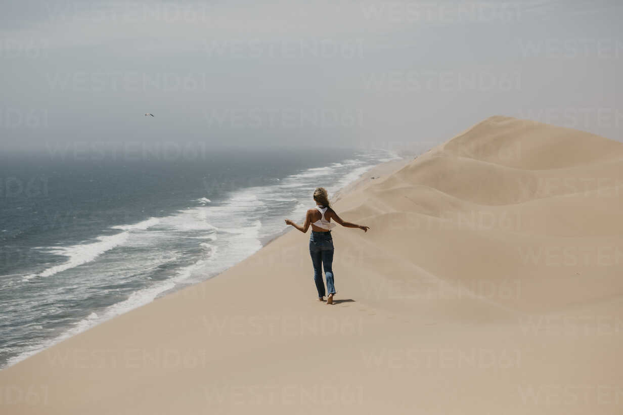 Namibia, Walvis Bay, Namib-Naukluft National Park, Sandwich Harbour, woman walking in dune landscape at the sea - LHPF00436 - letizia haessig photography/Westend61