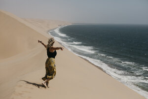 Namibia, Walvis Bay, Namib-Naukluft National Park, Sandwich Harbour, woman walking in dune landscape at the sea - LHPF00439