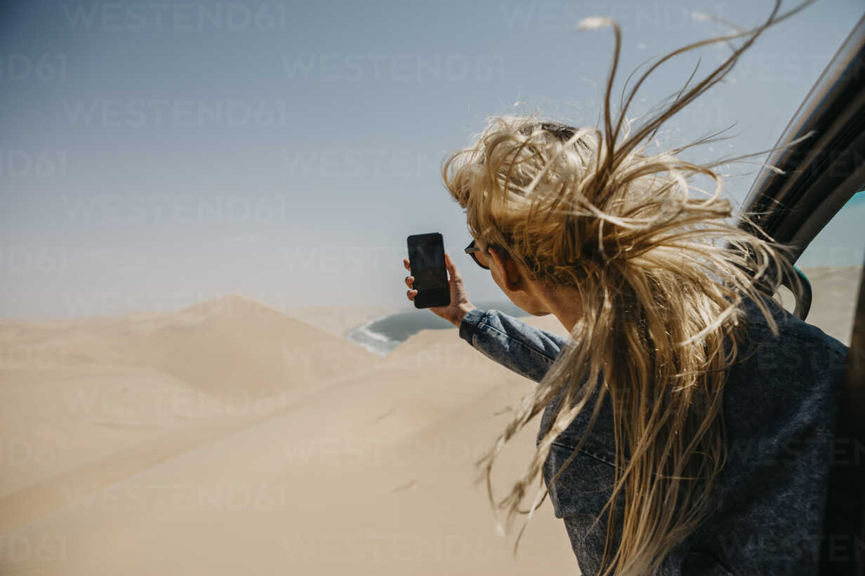Namibia, Walvis Bay, Namib-Naukluft National Park, Sandwich Harbour, woman leaning out of car window taking cell phone picture - LHPF00442 - letizia haessig photography/Westend61