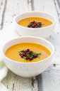 Bowls of carrot ginger coconut soup with topping of parsley and pomegranate seed - LVF07727